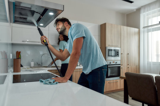 Young caucasian man in uniform cleaning kitchen range hood with steam cleaner while his smiling female colleague washing something in the sink on the background. Cleaning services concept