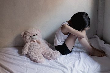 Sad little girl sitting in room. human trafficking concept.