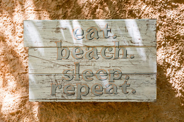 Relaxation, vacation idyllic background. Wooden board with words: eat beach sleep repeat.
