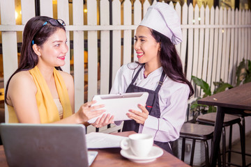 Woman and waitress smiling with tablet in cafe