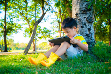 Adorable asian boy sweet casual sitting on green grass use tablet computer learnning nature tree