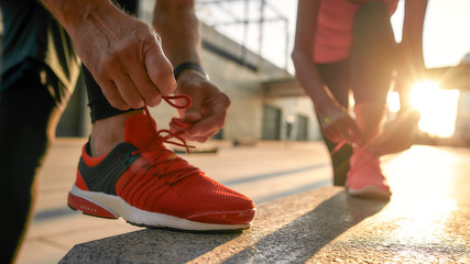 Exercising together. Close up photo of two people in sport clothes tying shoelaces before jogging outdoors. Fit, fitness, exercise