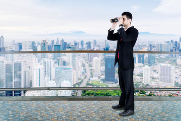 Male businessman using binocular looking for opportunity