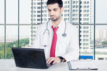 Male doctor working with laptop in hospital