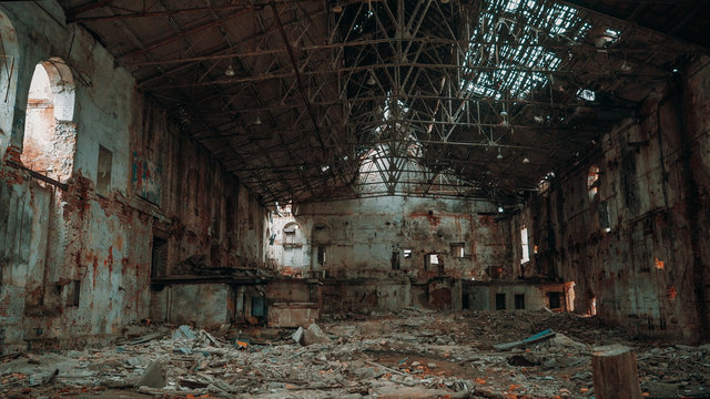 Inside ruined and abandoned large creepy industrial factory warehouse hangar, toned