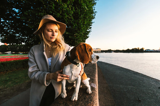 Thoughtful woman hugging dog leaning on fence and looking at river
