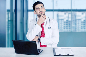 Young doctor thinking solution in healthcare center