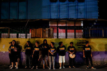 Members of a volunteer group of women take a break while patrolling with police officers on the streets of Pateros