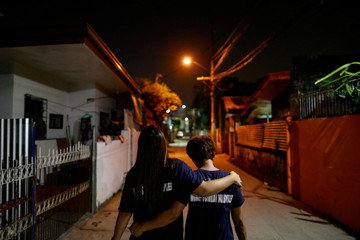 Two members of a volunteer group of women patrollers walk arm to arm while on duty in Pateros