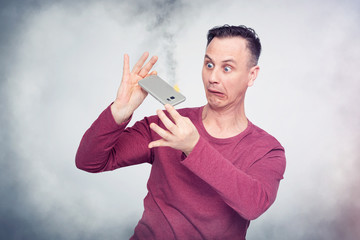 Man in horror looks at a smartphone burning in his hands. Mobile device fire situation