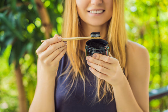 Young woman brush teeth using Activated charcoal powder for brushing and whitening teeth. Bamboo eco brush