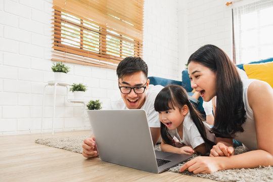 Asian family using laptop computer to surf internet / online shopping, happy family with technology concept