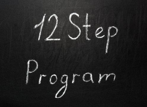 Twelve step program written in white chalk on a black chalkboard