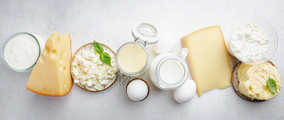Fresh dairy products, milk, cottage cheese, eggs, yogurt, sour cream and butter on white background, top view