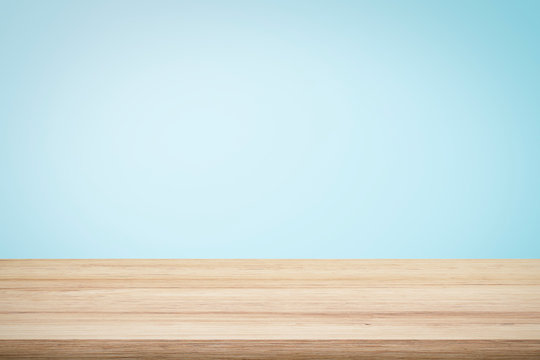 Empty wooden deck table over light blue wallpaper background for present product.