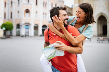 Happy young couple walking outdoors sightseeing and holding a map Wall mural