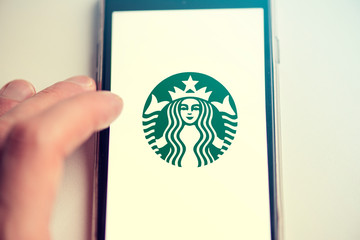 BERLIN - FEB 17: New Starbucks Logo on Screen of Mobile Phone in Berlin on February 17. 2020 in Germany. Toned Picture.