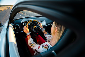From behind woman driver at the hands of the steering wheel of a sports car on a lonely road
