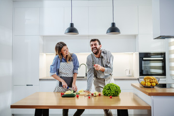 Young charming smiling caucasian woman in apron standing in kitchen and cutting cucumber while talking with her boyfriend. Man holding cherry tomato and talking about healthy lifestyle.