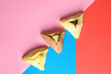 Purim holiday concept. Creative arrangement of variety Hamantash on red, pink and blue paper background. Hamantaschen triangular pastries also called Haman's pockets or Oznei Haman-Haman's ears.
