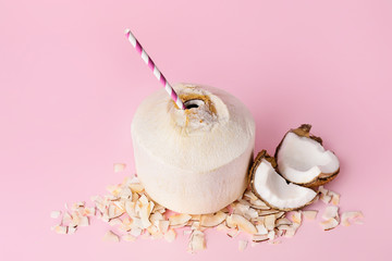 Young coconut with straw on color background