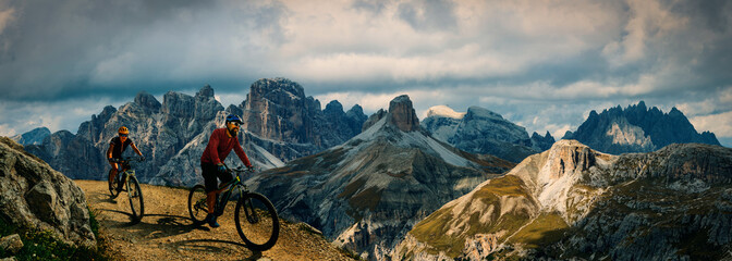 Photo sur Toile Taupe Cycling outdoor adventure in Dolomites. Cycling woman and man on electric mountain bikes in Dolomites landscape. Couple cycling MTB enduro trail track. Outdoor sport activity.