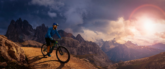 Cycling outdoor adventure. Man cycling on electric bike, rides mountain trail. Man riding on bike in Dolomites mountains landscape. Cycling e-mtb enduro trail track. Outdoor sport activity. Wall mural