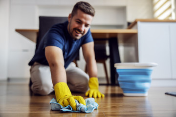 Obraz Man waxing parquet at home. Selective focus on hand with cloth. Rubber gloves on hands. Home interior. - fototapety do salonu