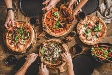 Canvas Prints Pizzeria Family or friends having pizza party dinner. Flat-lay of people taking and eating various kinds of pizza and drinking red wine over rustic wooden table, top view. Fast food lunch, celebration