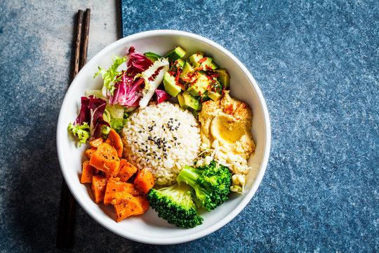 Vegan rice and vegetables salad, top view. Macrobiotic set with rice, hummus, avocado, broccoli and sweet potato.