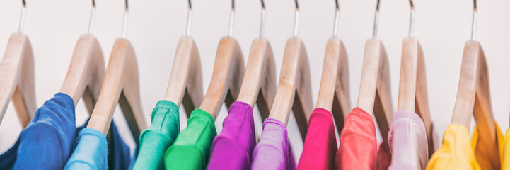 Clothes on clothing rack panoramic banner. Women's wardrobe fashion apparel rainbow organized t-shirts by colors hanging on closet hangers. Shopping spring cleaning. Panorama background.