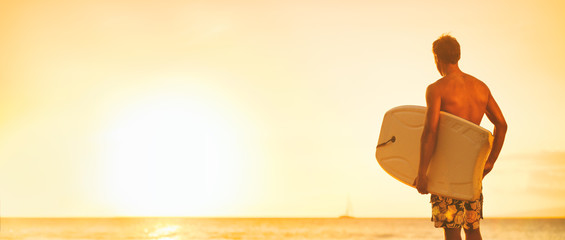 Beach surfer guy looking at ocean going surfing with bodyboard surfboard surf watersport summer travel lifestyle panoramic header for Hawaii sports.