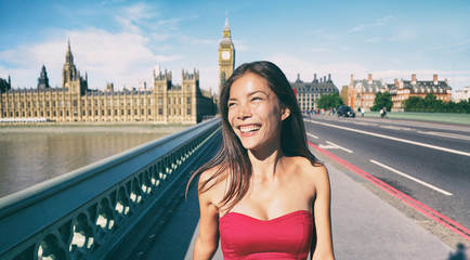 London Asian woman smiling happy in summer walking at Big Ben Westminster Bridge, England, UK. Traveler tourist tourism lifestyle concept with cheerful mixed race model.
