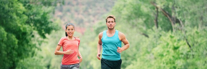 Running couple on trail run in forest park banner panoramic header. Fit athletes runners man and woman training partners friends jogging together in summer outdoors.