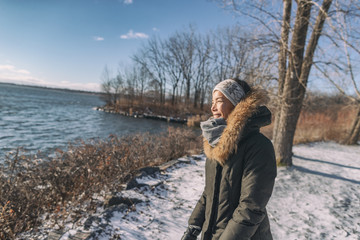 Winter cold Asian woman happy smiling in cold weather on outdoor walk sunlight in forest nature active healthy lifestyle. Young girl enjoying outside leisure walking.