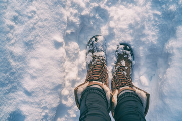 Winter hiking in Snow boots walking first person POV selfie of feet in deep cold snowfall in outdoors forest. Girl taking picture of her shoes.