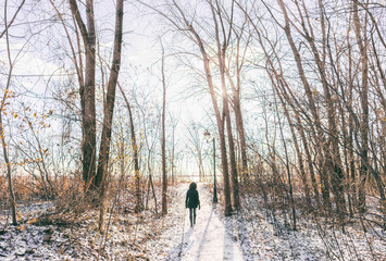 Winter city park outdoor walk woman walking in snow in snowy forest path in sunny day, active people. Outside leisure. girl hiking in nature.