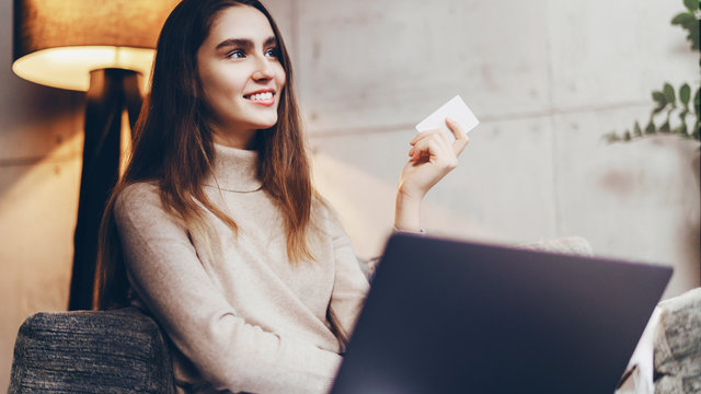 Girl using bank card for buying things online. Retail stores offering bonus cards for customers. Select items in web shop app, transfer money safely using sms code for payment.