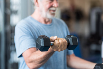 close up of mature man holding two dumbbells doing exercise at the gym to be healthy and fitness - portrait of active senior lifting weight