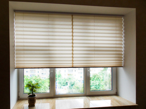 Pleated blinds XL Coulisse, beige color, with 50mm fold closeup in the window opening in the interior. Home blinds - modern bottom up privacy shades half raised on apartment windows.