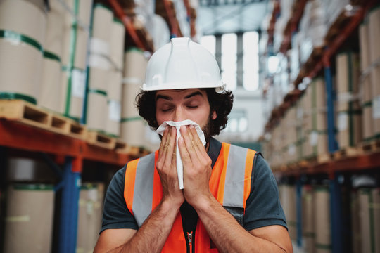 Young warehouse manager coughing and sneezing while feeling sick and covering mouth with handkerchief standing in factory