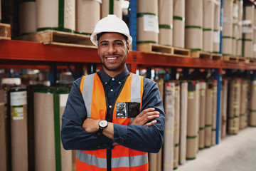 Fototapeta Confident african american man standing with folded arms in manufacturing unit with white helmet and uniform in factory obraz
