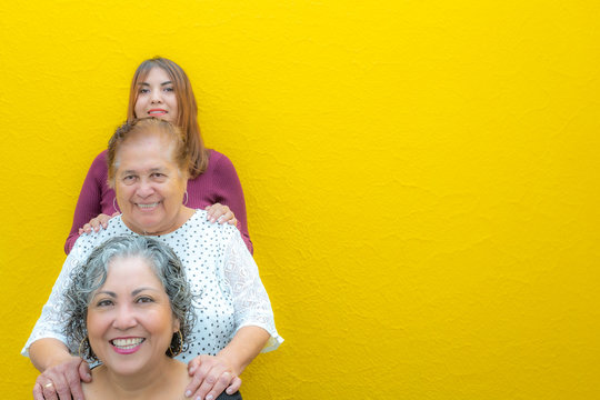 Three generations of latin Mexican women smiling in line, daughter, grandmother and granddaughter wearing casual clothes looking at the camera with a yellow background, space for text