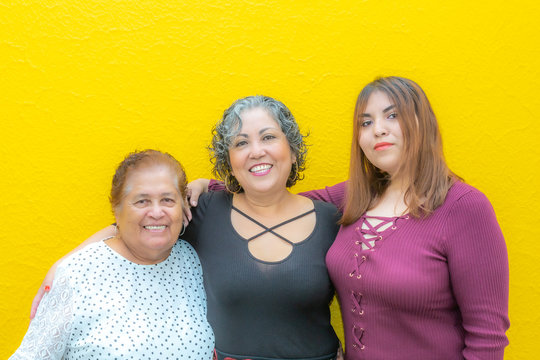 Three generations of latin Mexican women smiling, grandmother, daughter and granddaughter wearing casual clothes looking at the camera with a yellow background