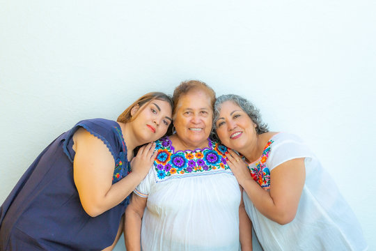 Three generations of smiling Mexican women, mother and daughter leaning on grandma, blouses with floral prints on a white background