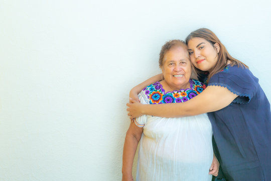 Granddaughter hugging her grandmother, two smiling Mexican women on a white background, space for text