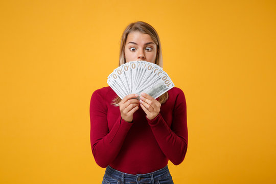 Shocked young blonde woman girl in casual clothes posing isolated on yellow orange background studio portrait. People lifestyle concept. Mock up copy space. Hold fan of cash money in dollar banknotes.