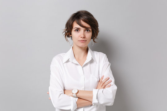 Beautiful young business woman in white shirt posing isolated on grey background studio portrait. Achievement career wealth business concept. Mock up copy space. Holding hands crossed, looking camera.