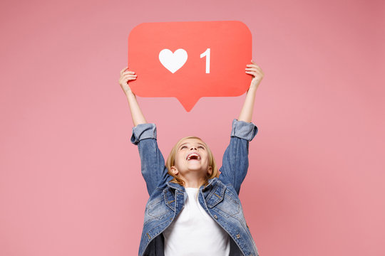 Cheerful little kid girl 12-13 years old in denim jacket isolated on pastel pink background in studio. Childhood lifestyle concept. Mock up copy space. Hold huge like sign from Instagram heart form.