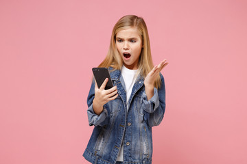 Shocked irritated little kid girl 12-13 years old in denim jacket posing isolated on pastel pink background. Childhood lifestyle concept. Mock up copy space. Using mobile phone, typing sms message.